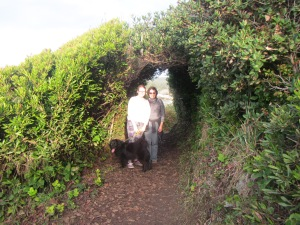 Friends framed by hedge archway