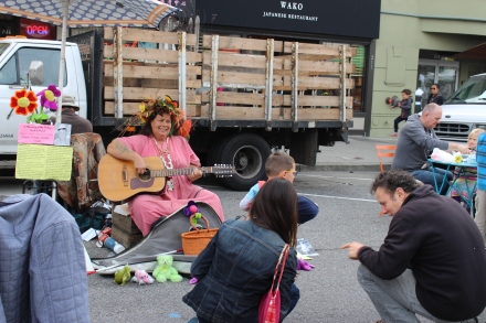 Performer serenades children at Farmers Market.