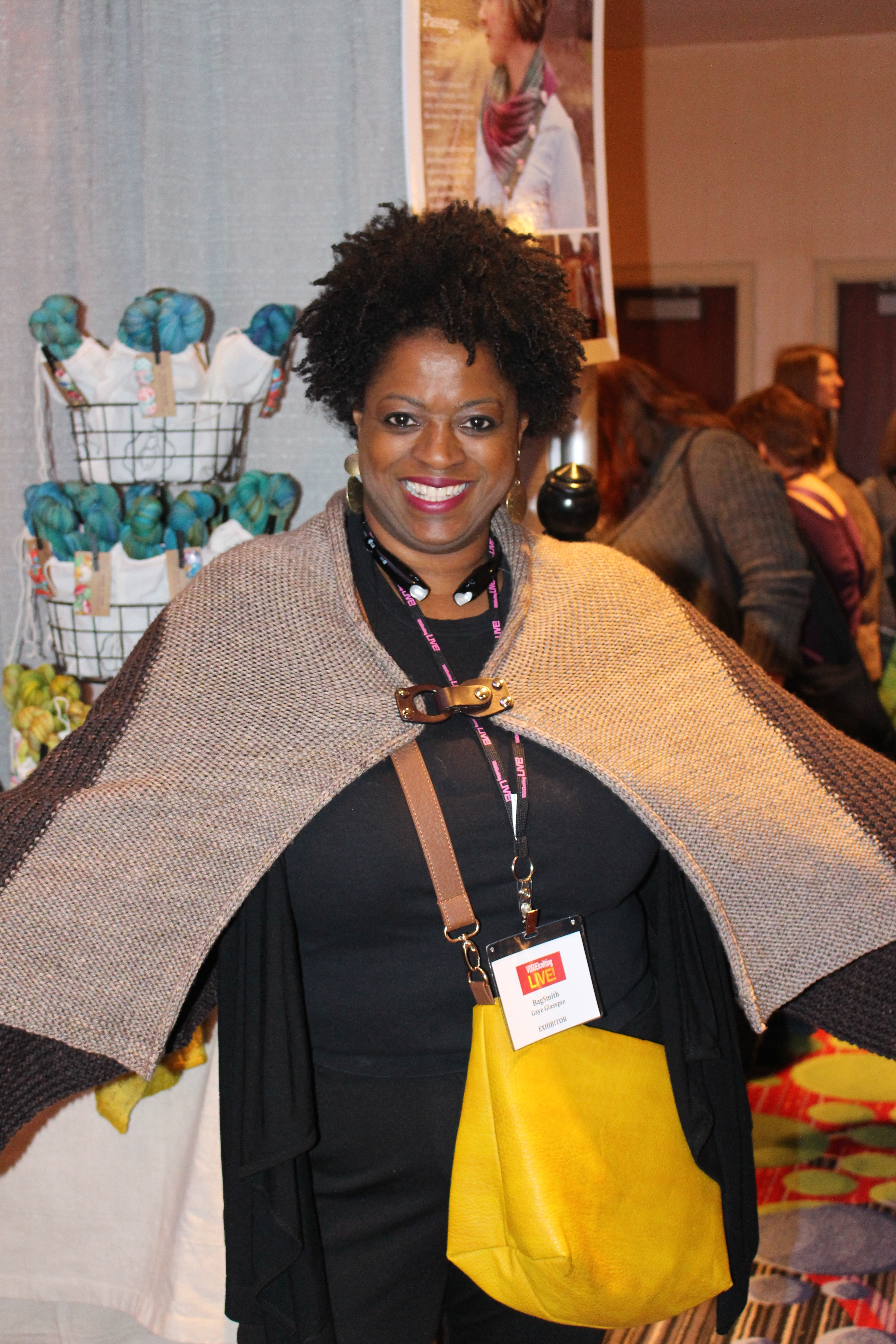 3fd215ea6111 Knitter tries on Heidi   Lana s sample shawl with cool buckle.