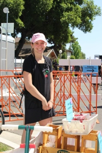 Cheerful young woman selling water and cherries.